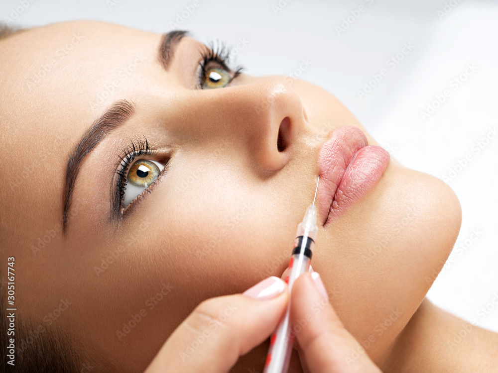 Fototapeta woman gets botox injection in her face