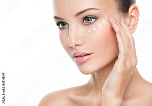 woman with healthy face applying cosmetic cream under the eyes Fototapeta