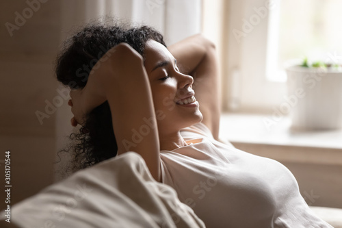 Fotomural  Happy biracial woman relax on couch with eyes closed
