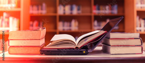 Stack of books with laptop on table in library. Canvas Print