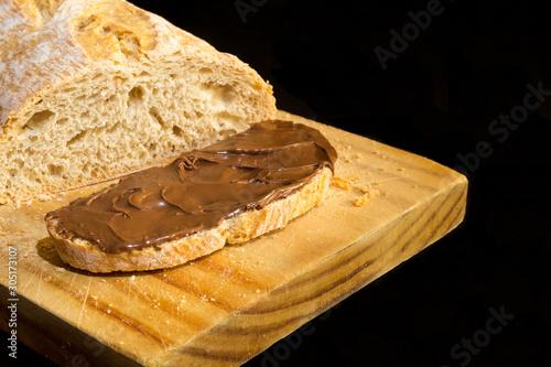 rebanada de pan artesano de espelta con crema de cacao sobre fondo negro Wallpaper Mural
