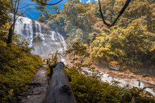 The Blurred Background Of Water Droplets From The Waterfalls That Cover The Area Around The Walkway, Surrounded By Large Trees And Fresh Cool Air While Visiting The Scenery.