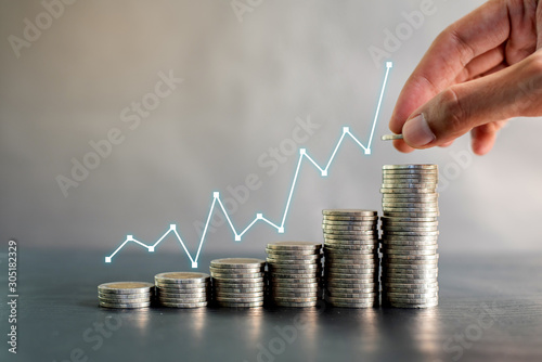 Cuadros en Lienzo Hand stacking coins on black wooden table with profit line chart growth up
