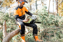 Portrait Of A Professional Lumberman In Protective Workwear Sitting With Mobile Phone On The Felled Tree, Resting After The Hard Work In The Forest