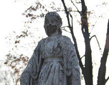 Monument And Candles In The Cemetery. All Saints Day In Poland. Stone Statue In The Cemetery. Stone Statue In The Cemetery. Close-up. Disfigured Face Statue.