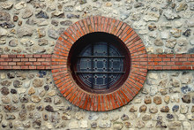 Circle Porthole Window With Bars And Ornaments On Wall And Stone And Bricks Around