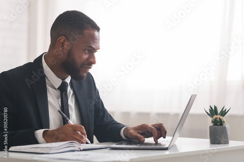 Concentrated business clerk making notes, using laptop