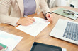 High angle closeup of successful businesswoman reading documents while working at desk in office, copy space