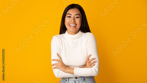 Fotografia Happy asian girl posing with crossed arms