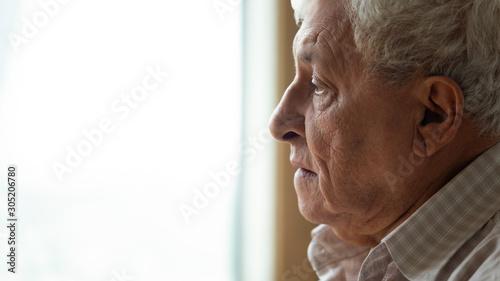 Pensive older man looking out of window, recollecting memories. Wallpaper Mural