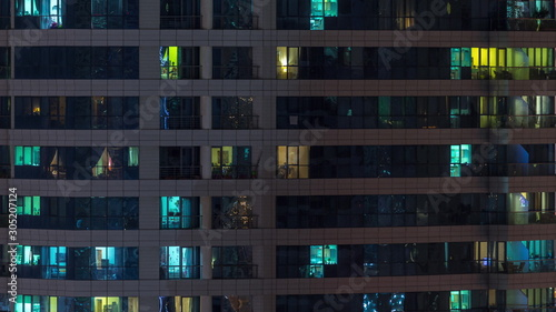 Rows of glowing windows with people in apartment building at night Wallpaper Mural