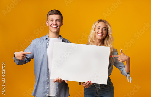 Obraz Young couple holding blank advertising board and pointing on it - fototapety do salonu