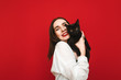 Portrait of a joyful girl hugging with a cute black cat on a red background, looking into the camera and smiling. Happy lady in a white shirt hugs a pet animal. Isolated.