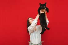Happy Girl Holds A Frightened Black Cat In Her Hands And Lifts It Up, She Plays With It, The Pet Looks Into The Camera. Owner Plays With A Cat On A Red Background. Isolated On Red Background.