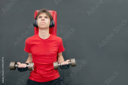 young man in sports clothes and headphones is engaged with dumbbells in the gym Canvas Print