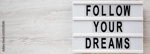 'Follow your dreams' words on a lightbox on a white wooden surface, top view Wallpaper Mural