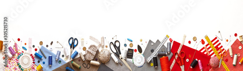 Panoramic view on sewing composition with threads, fabrics, scissors, buttons, needles and other sewing accessories on white background Fototapeta