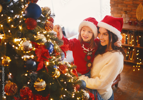 Obraz Smiling mother and daughter decorating Christmas tree - fototapety do salonu
