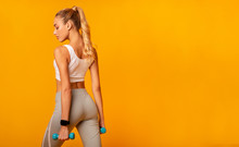 Girl Holding Dumbbells Standing Back To Camera Over Yellow Background