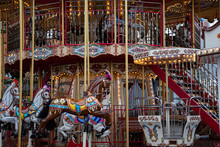 Carousel In Park. Gorgeous Vintage Carousel With Toy Horses And Shiny Golden Lights. Circle Merry-go-round At Funfair In European City. Fairytale Retro Ornate Roundabout Swings. Happiness Concept