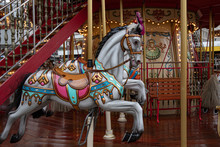 Merry Go Round. Fairytale Painted White Toy Horse Of Vintage Carousel In French Style. Retro Colorful Illuminated Merry-go-round With Golden Shiny Lights. Kids Playground At Christmas Market In Europe