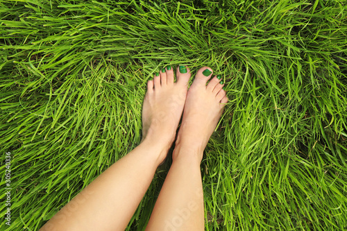 Valokuvatapetti Pedicure with green nail Polish on the background of young grass in summer on the lawn