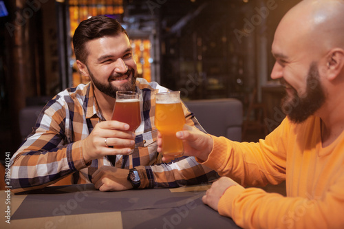 Photo Cheerful male friends clinking their beer glasses, celebrating at the pub