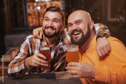 Happy bearded man enjoying drinking beer with his best friend Wallpaper Mural