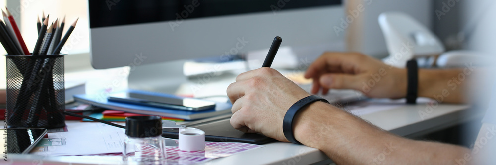 Fototapeta Designer male arm hold graphic pad pen working on project