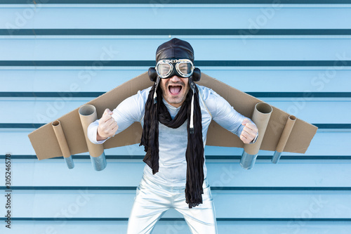 Photo man in silver suit with glasses and aviator helmet and cardboard plane wings