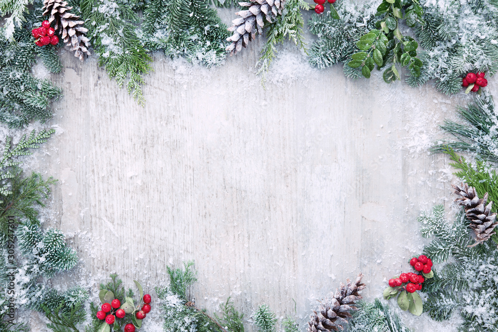 Fototapeta Christmas and New Year background with fir branches and snowfall on wooden white board