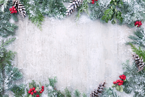 Poster Countryside Christmas and New Year background with fir branches and snowfall on wooden white board