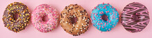 Different Types Of A Colorful Donats Decorated Sprinkles And Icing On Blue Background, Long Banner