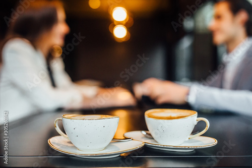 Pinturas sobre lienzo  Close up image of two coffee cups with latte on wooden table in cafe