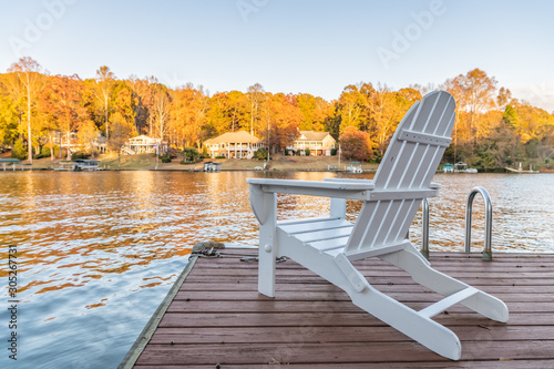 Photo Adirondack style chairs on a dock, overlooking a beautiful, quiet, lake