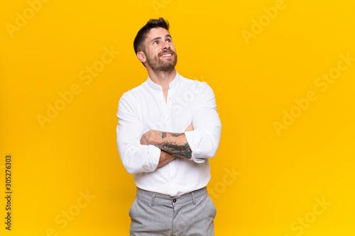 Photo young handosme man feeling happy, proud and hopeful, wondering or thinking, look