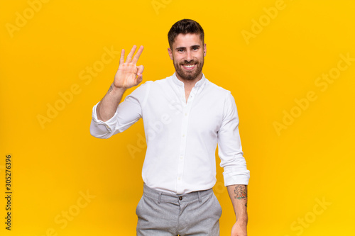 Obraz na plátně  young handosme man feeling happy, relaxed and satisfied, showing approval with o
