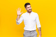 Young Handosme Man Smiling Happily And Cheerfully, Waving Hand, Welcoming And Greeting You, Or Saying Goodbye Against Flat Color Wall