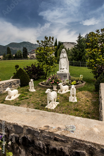 Fotomural Statue of Bernadette of Lourdes with sheep in Lourdes
