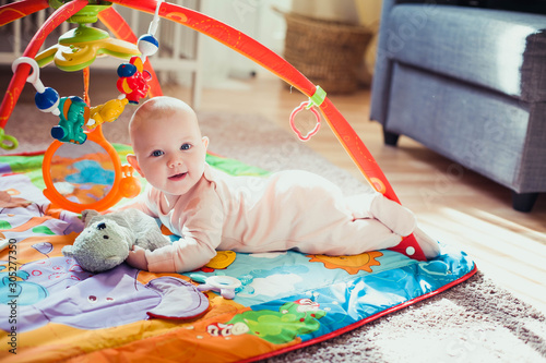 Obraz 4 months old baby girl lying on colorful play mat on the floor. Activity carpet for kids. - fototapety do salonu