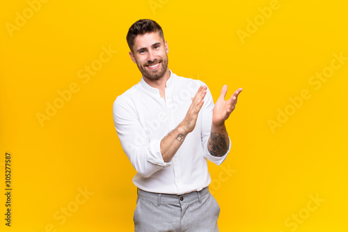 Photo young handosme man feeling happy and successful, smiling and clapping hands, say