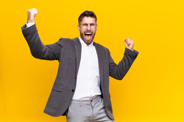 young handosme man shouting triumphantly, looking like excited, happy and surprised winner, celebrating against flat color wall