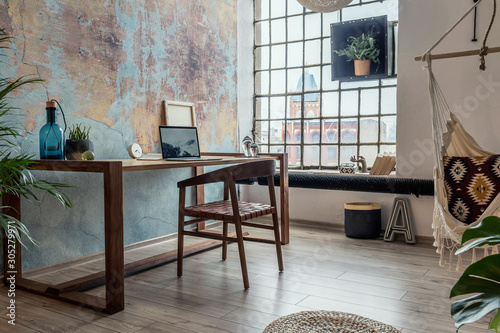 Obraz Stylish interior design of office space in loft apartment with wooden desk, chair, office supplies, laptop, plants, hammock  and elegant accessories. Modern home office decor. Bright space. Template. - fototapety do salonu