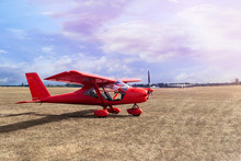 Small Private Red Aircrafts Parked At Ground At Pink Sunset. Red Plane On Field  Copy Space.