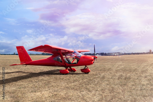 Small private red aircrafts parked at ground at pink sunset Fototapeta