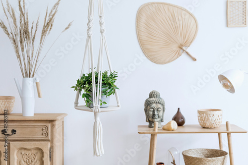 Foto Minimalistic boho interior with design and handmade macrame shelf planter hanger for indoor plants, wooden furnitures, elegant accessories ,rattan basket and leaf