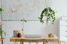 Stylish And Boho Home Interior Of Living Room With Wooden Desk, Laptop, White Lamp, Macrame Shelf And Desk Supplies. Design And Elegant Accessories. Modern Home Decor. Abstract Painting On The Wall.