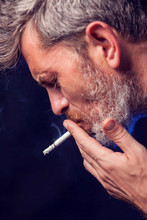 A Portrait Of The Man Smokes Cigarette On Black Background. Nicotine Addiction Concept