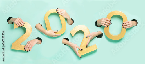 Female hands hold golden new year 2020 digits through a hole on neon mint background Canvas Print