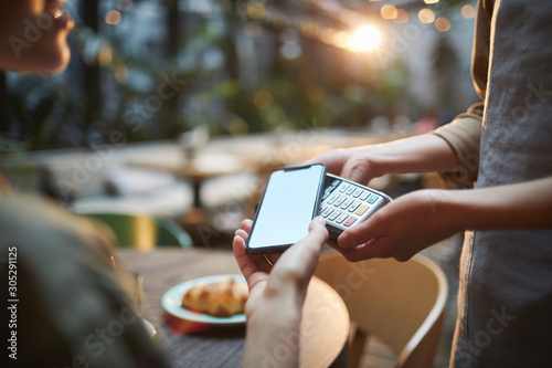 Fototapety, obrazy: Close up of young woman paying via NFC in cafe, focus on female hands holding smartphone with blank screen to banking terminal, copy space